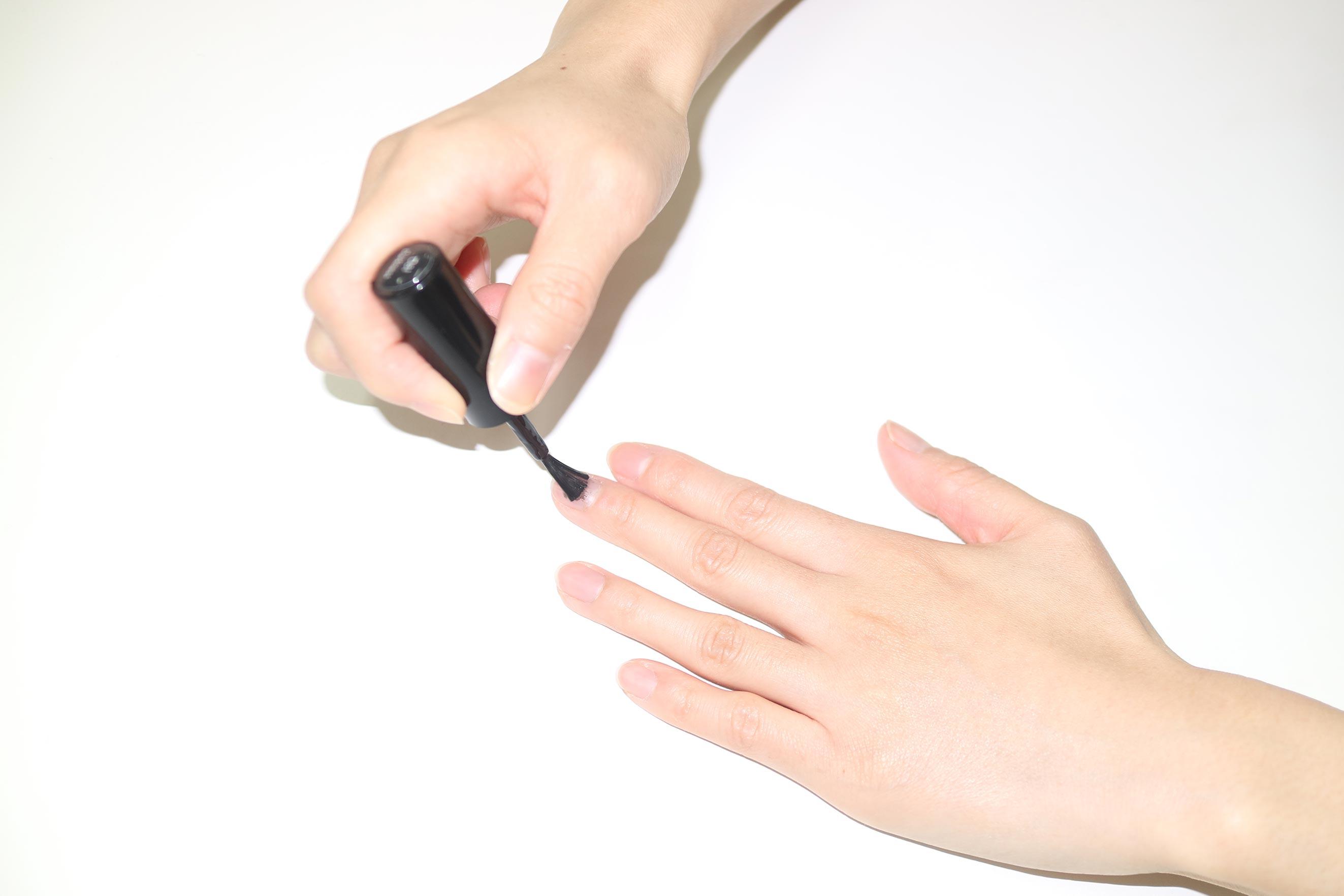 テーブルの上に手を置いて、ブラシを上から押し付けてジェルネイルを塗る